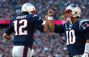 Nov 23, 2014; Foxborough, MA, USA; New England Patriots quarterback Jimmy Garoppolo (10) congratulates quarterback Tom Brady (12) after a touchdown during the second quarter against the Detroit Lions at Gillette Stadium. Mandatory Credit: Greg M. Cooper-USA TODAY Sports